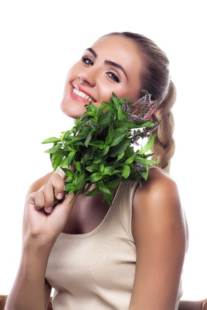 Close-up portrait of happy young woman with a bundle of fresh mint. Concept vegetarian dieting - healthy food Stock Photo