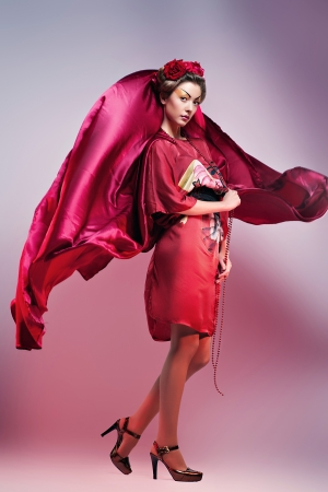 Fashion asian woman wearing traditional japanese red kimono, studio shot. Geisha photo