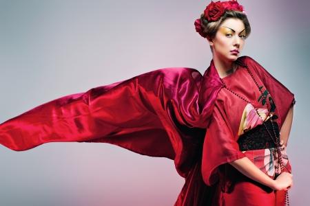 Fashion asian woman wearing traditional japanese red kimono, studio shot. Geisha photo