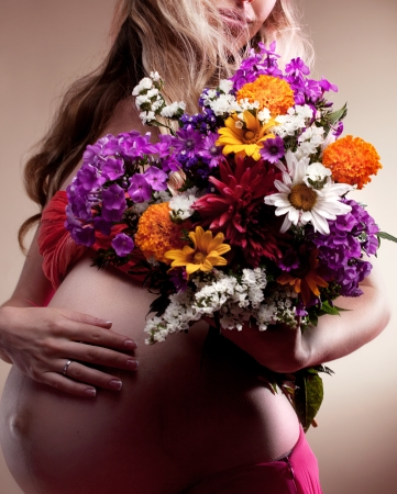 body care: Beautiful Pregnant woman holding spring flowers Stock Photo