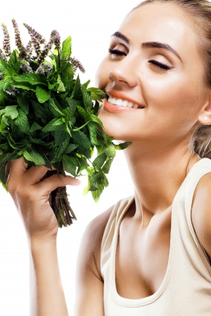 Portrait of happy young woman with a bundle of fresh mint  Concept vegetarian dieting - healthy food Stock Photo