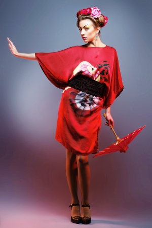 Fashion asian woman wearing traditional japanese red kimono, studio shot  Geisha photo