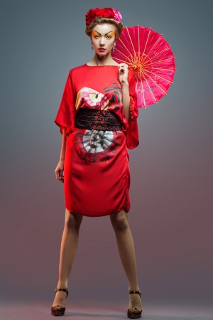 Fashion asian woman wearing traditional japanese red kimono  with umbrella, studio shot   Geisha photo