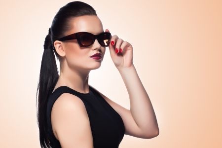 close-up portrait of beautiful and fashion girl in sunglasses, studio shot  Professional makeup and hairstyle photo