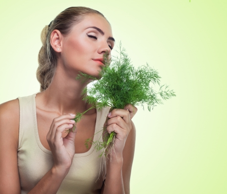 Close-up portrait of happy young woman with  bundle herbs  dill  in hands on white background   Concept vegetarian dieting - healthy food
