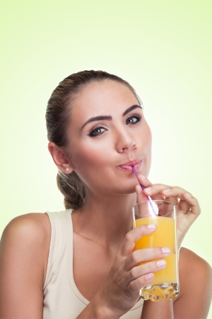 Close-up portrait of happy young woman with juice on white background   Concept vegetarian dieting - healthy food