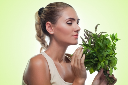 Close-up portrait of happy young woman with a bundle of fresh mint  Concept vegetarian dieting - healthy food Stock Photo