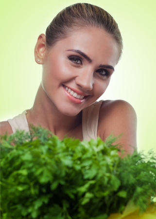 Close-up portrait of happy young woman with bundle herbs  salad  in hands on white background  Concept vegetarian dieting - healthy food Stock Photo