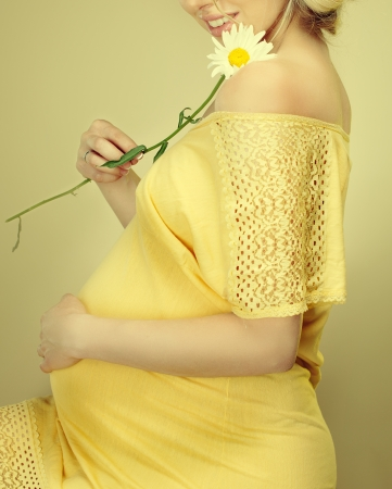 Beautiful Pregnant woman holding spring flowers photo
