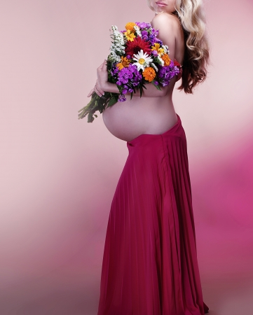 Beautiful Pregnant woman holding spring flowers Stock Photo