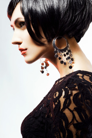 Studio shot of Sexy Fashiol Woman in Black Dress and jewelry. Professional Makeup and Hairstyle