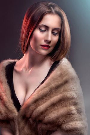 Fashion woman wearing in winter fur coat  on blur background photo
