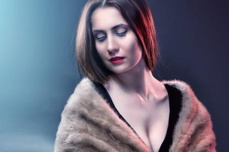 Fashion woman wearing in winter fur coat  on blur background photo