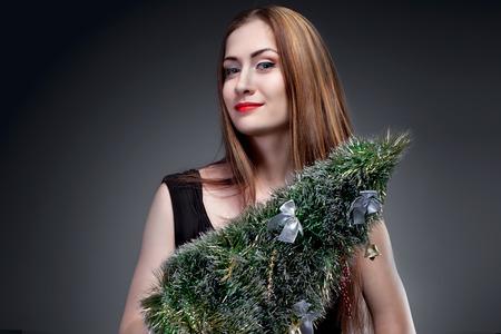 Fashion woman holding christmass tree  on blur background