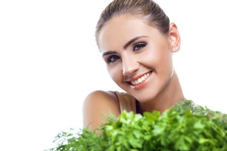Close-up portrait of happy young woman with  bundle herbs (salat) in hands on white background.  Concept vegetarian dieting - healthy food