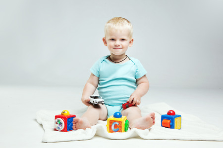 Smiling Baby boy is  playing with educational toys