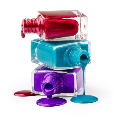 cosmetic lacquer: Bottles with spilled nail polish over white background