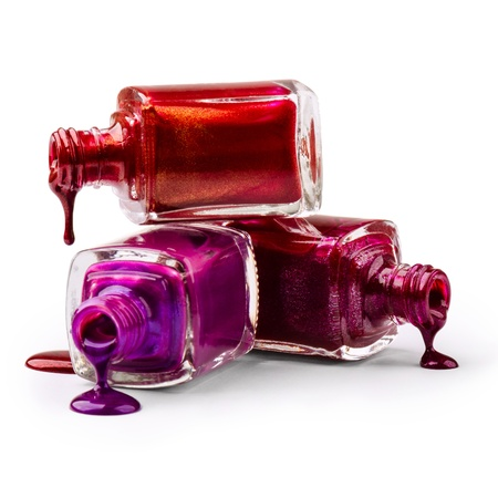 salon: Bottles with spilled nail polish over white background