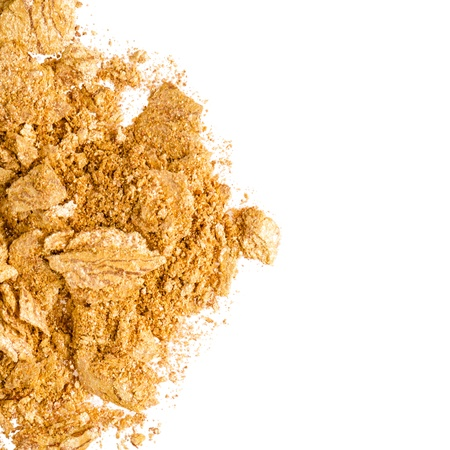 Crushed gold eyeshadow on white Stock Photo