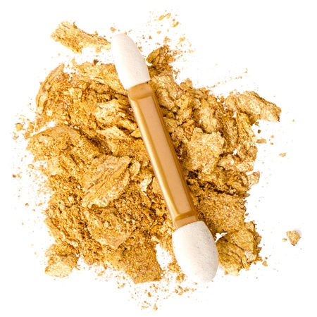 crumbled: Crushed gold eyeshadow on white Stock Photo