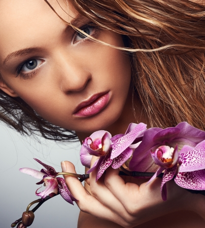 Portrait of young beauty with orchid photo