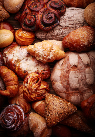 bakery products: Fresh tasty bread and buns over wooden background Stock Photo
