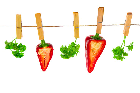 ingridients: Fresh pepper hang on clothes-pins on isolated white  Stock Photo