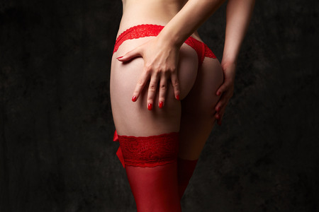 Woman's ass in red lace panty on grey background Banque d'images