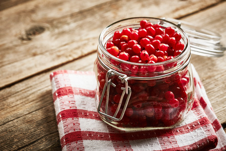 guelder rose berry: Jar with homemade viburnum jam on wooden background