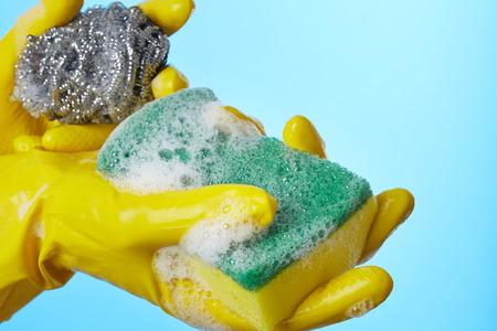 lavare piatti: Mani della donna in guanti con spugna per lavare i piatti Archivio Fotografico