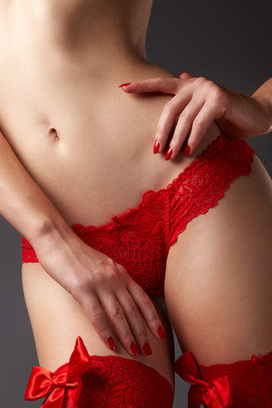 Womans body in red lace underwear on grey background photo
