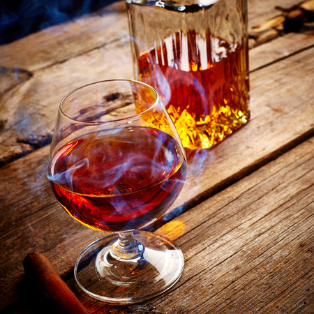 drunks: Vintage Cognac and cigar on wooden background Stock Photo