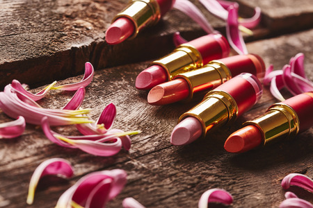 Lipsticks with flower petals on wooden