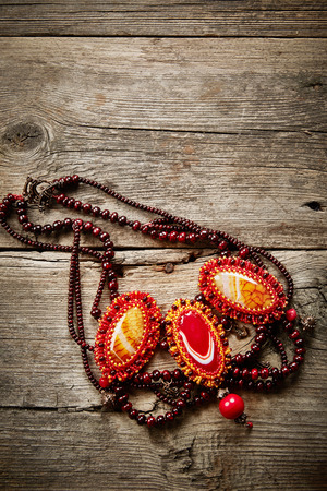 Beautiful handmade necklace on wooden background photo