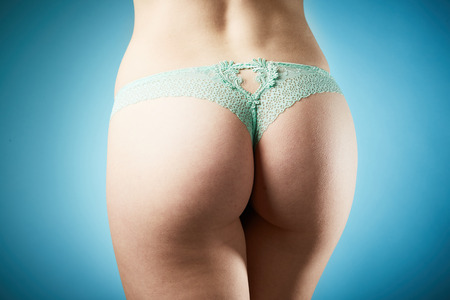 Woman ass in green panties on blue background