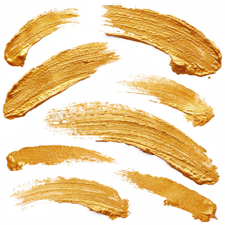 Strokes of golden paint isolated on white background Standard-Bild