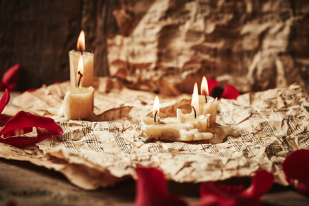 octaves: Vintage music sheets with rose petals and candles on wooden background
