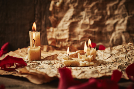 Vintage music sheets with rose petals and candles on wooden background photo