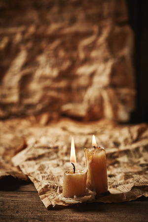 octaves: Vintage music sheets with candle on wooden background Stock Photo