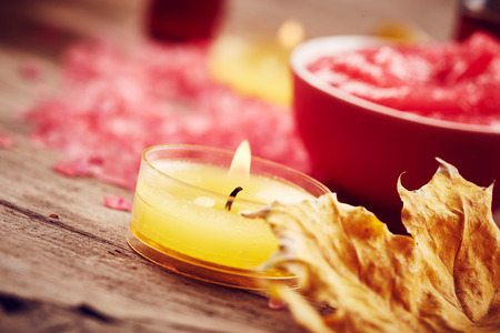 Spa still life with candle and autumn leaves on wooden background