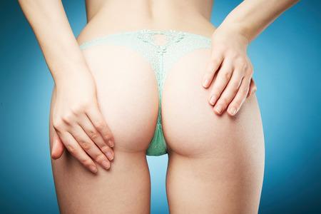 culo donna: Giovane corpo della donna in mutandine piuttosto su sfondo blu