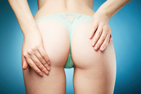 teen underwear: Young woman body in pretty panties on blue background