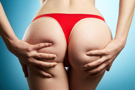 Womans ass in red panties on blue background