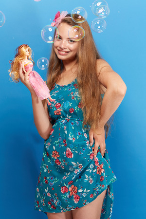 Pretty girl with barbie on blue background photo