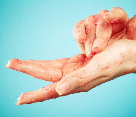 Womans hands in body scrub on blue background