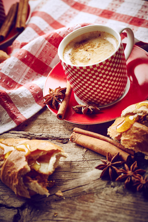 Coffee still life with croissant on wooden background photo