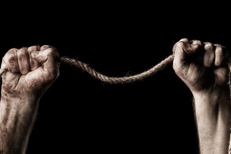 aggression: Male hand with rope on black . Conception aggression Stock Photo