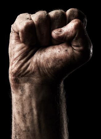 Male clenched fist on black background photo