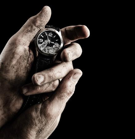 black clock hands: Clock in male hands on black background