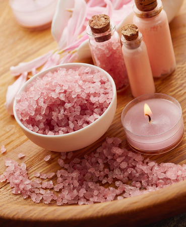 spa still life: Spa still life with pink sea salt and flower petals on wooden background
